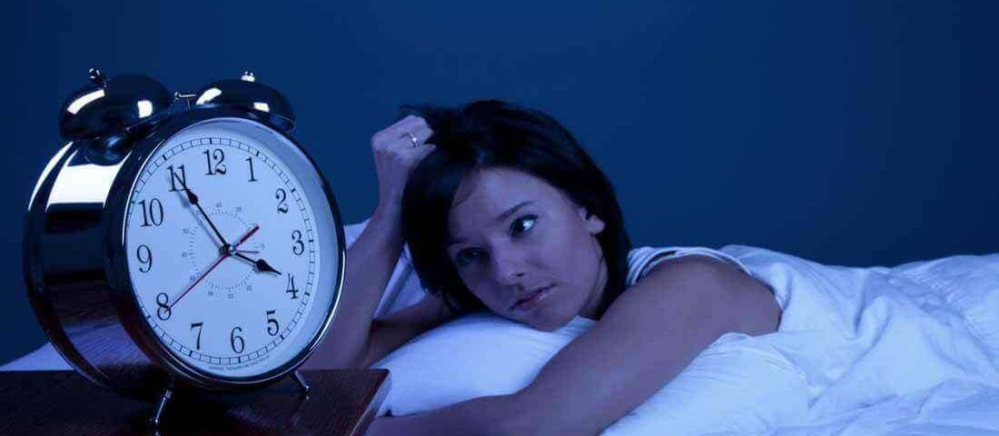 Women having sleeping problem in midnight lying on bed